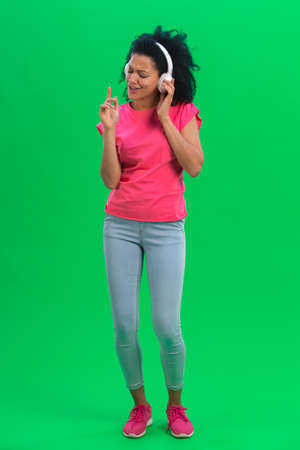 Portrait of young female African American dancing and enjoying music in big white headphones. Black woman with curly hair in pink tshirt and jeans poses on green screen in the studio. Full length.