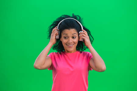 Portrait of young female African American enjoying music in big white headphones. Black woman with curly hair in pink tshirt poses on green screen in the studio. Close up.