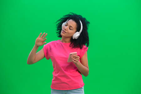 Portrait of young female African American enjoying music in big white headphones using smartphone. Black woman with curly hair poses on green screen in the studio. Close up. 스톡 콘텐츠