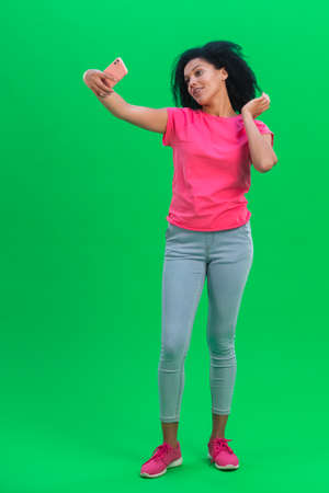 Portrait of young female African American making selfie on mobile phone. Black woman with curly hair poses on green screen in the studio. Full length.