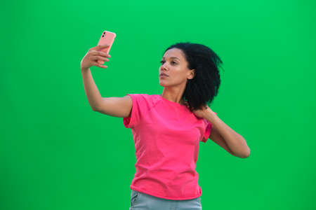 Portrait of young female African American making selfie on mobile phone. Black woman with curly hair in pink tshirt poses on green screen in the studio. Close up.