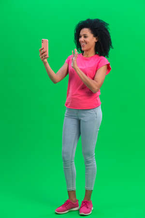 Portrait of young female African American talking for video chat using mobile phone and rejoice. Black woman with curly hair in pink tshirt and jeans poses on green screen in the studio. Full length.