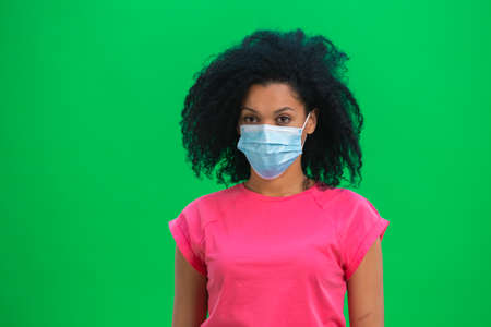 Portrait of young female African American looking at the camera in medical mask. Black woman with curly hair in pink tshirt poses on green screen in the studio. Close up.