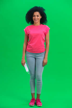 Portrait of young female African American looking at the camera holding a medical mask and smiling. Black woman with curly hair in pink tshirt poses on green screen in the studio. Full length.
