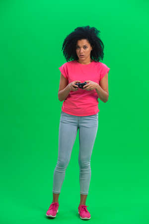 Portrait of young female African American playing a video game using a wireless controller. Black woman with curly hair in pink tshirt poses on green screen in the studio. Full length.