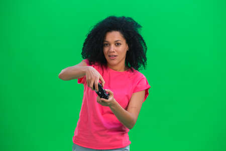 Portrait of young female African American playing a video game using a wireless controller. Black woman with curly hair in pink tshirt poses on green screen in the studio. Close up. 스톡 콘텐츠