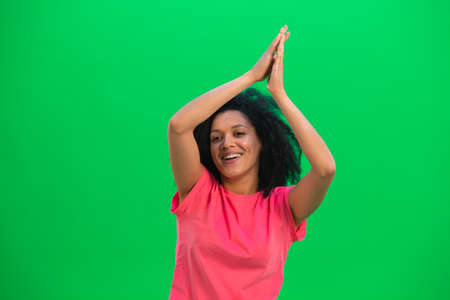 Portrait of young female African American smiling happily, raising your hands up and folding them with your palms. Black woman with curly hair in pink tshirt poses on green screen in studio. Close up.