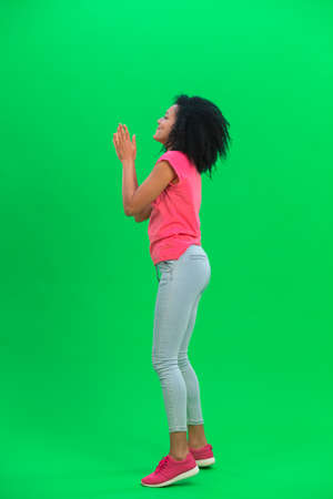 Portrait of young female African American keeping palm together and asking for something. Black woman with curly hair in pink tshirt poses on green screen in the studio. Side view. Full length.