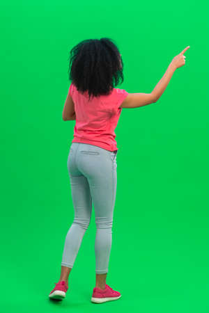 Back view of young female African American considering and choosing something. Black woman with curly hair in pink tshirt and jeans poses on green screen in the studio. Full length.