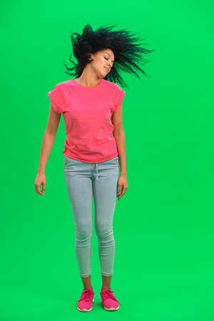 Portrait of young female African American waves curly hair. Black woman in pink tshirt and jeans poses on green screen in the studio. Full length.
