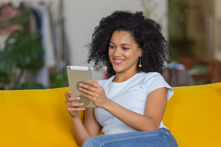 Portrait of a young African American woman talking on a video call on her digital tablet. Brunette with curly hair sitting on yellow sofa in a bright home room. Close up.