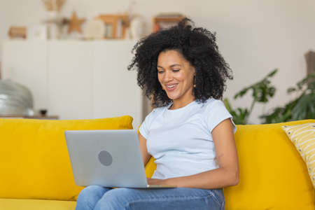 Portrait of a young African American woman talking on a video call on portable laptop. Brunette with curly hair sitting on yellow sofa in a bright home room. Close up.