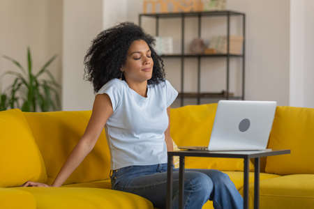 Portrait of a young tired African American woman sitting with closed eyes near the laptop. Brunette with curly hair posing on yellow sofa in a bright home room. Close up.