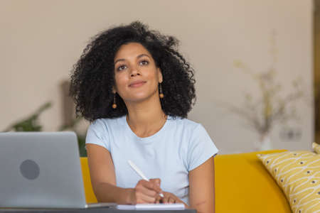 Portrait of a young African American woman talks on a video conference using a laptop and makes notes in a notebook. Brunette with curly hair sitting on yellow sofa in a bright home room. Close up.