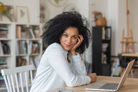 Portrait of young African American woman looking at camera and smiling. Brunette with curly hair in white blouse sits at table in light home office. Distance learning or remote work concept. Close up.