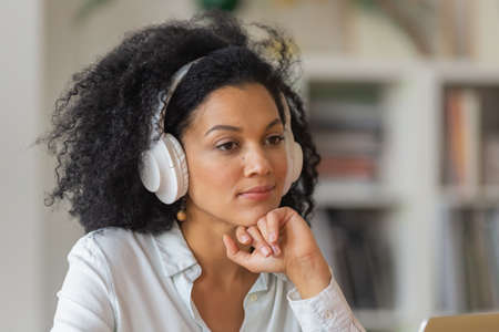 Portrait of African American woman listening to information or music in large white wireless headphones. Brunette sits at table in home office. Close up.