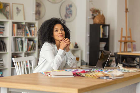 Portrait of a young African American woman looking at the camera. Female designer in white blouse sits at a table in office near color palette and samples of fabrics for a design project. Close up.