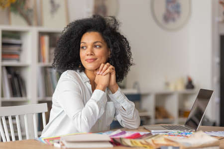 Portrait of a young African American woman looking to the side. Female designer in white blouse sits at a table in office near color palette and samples of fabrics for a design project. Close up.