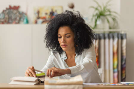 Portrait of a young African American woman looking through the color palette and samples of fabrics for a design project. Female designer in white blouse sits at a table in light office. Close up.