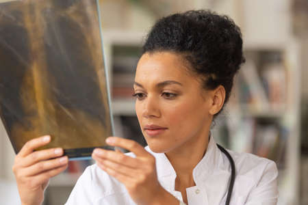 A young female doctor examining snapshot of lungs. Afro American woman sits at table in a hospital office. Telemedicine. Online doctor appointment. Close up.