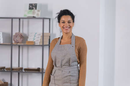 Pretty African American woman looking at the camera and smiling cute. Young female owner of an online store in an apron posing against the backdrop of shelves with goods. Close up.