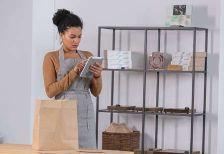 Pretty African American woman is packing goods in paper bag for customer. Young female owner of an online store prepares parcel for delivery, checking the data on tablet.