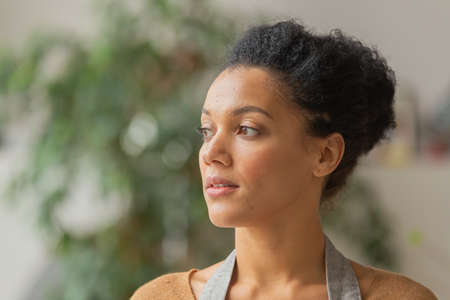 Portrait of a young African American woman looking to the side. Young female owner of an online store in an apron posing against on a blurred background. Close up.