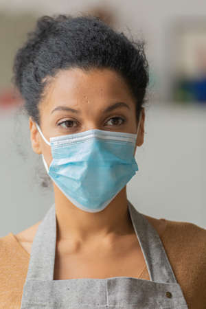 Pretty African American woman in medical mask. Young female mixed race posing in an apron against the backdrop of a light room. Close up. 스톡 콘텐츠