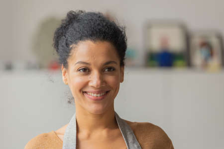 Portrait of a young African American woman looking to the side and smiling. Young female owner of an online store in an apron posing against on a blurred background. Close up.