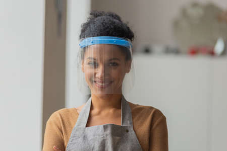 Pretty African American woman looking at the camera wearing a protective plastic mask and smiling. Young female mixed race posing against the backdrop of a light room. Close up.