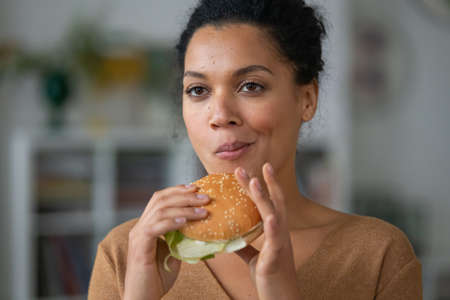 Portrait of pretty African American woman with an appetite for biting a hamburger. Young mixed race female eats fast food and poses against a blurred background of a light room. Close up.