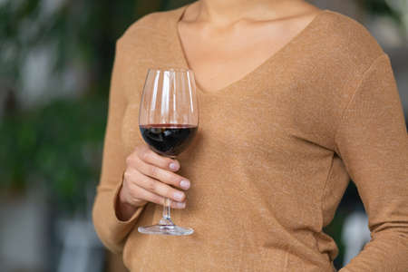 Portrait of unrecognizable woman with a glass of red wine in her hand. Mixed race female posing against blurred background of light room with green plants. Close up.