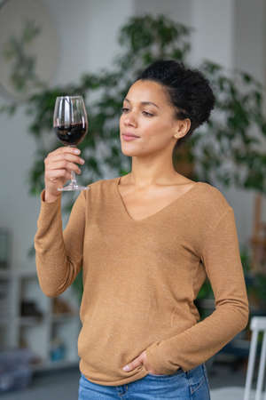 Portrait of a young African American woman looking at a glass of red wine. Cute mixed race female posing against blurred background of light room with green plants. Close up.