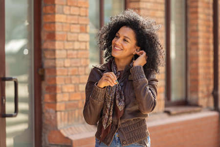 Portrait of young African American woman cute smiling. Brunette with curly hair in leather jacket posing on street against backdrop of blurred brick building. Close up