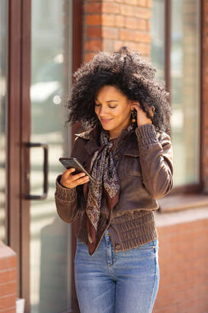Portrait of young African American woman texting on her smartphone and smiling. Brunette with curly hair in leather jacket and stylish jeans posing on street against backdrop of blurred brick building.