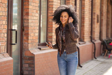 Portrait of young African American woman cute smiling. Brunette with curly hair in leather jacket posing on street against backdrop of blurred brick building. Close up.