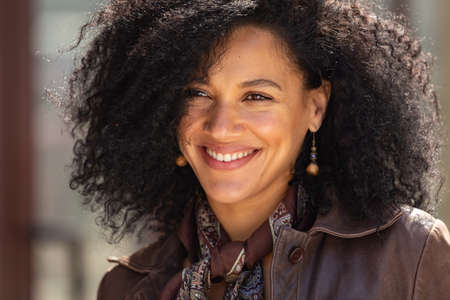 Portrait of stylish young African American woman smiling happily. Brunette with curly hair in brown leather jacket posing on street against backdrop of blurred brick building. Close up.
