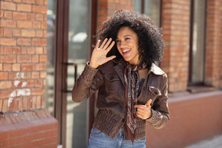 Portrait of stylish young African American woman waving hello and smiling. Brunette with curly hair in brown leather jacket posing on street against backdrop of blurred brick building. Close up. 스톡 콘텐츠