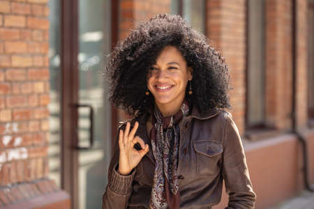 Portrait of stylish young African American woman making sign ok and smiling. Brunette with curly hair in brown leather jacket posing on street against backdrop of blurred brick building. Close up. 스톡 콘텐츠
