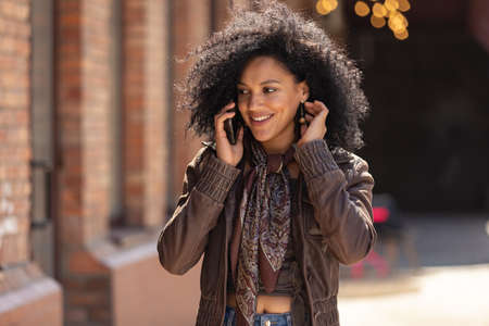 Portrait of young African American woman talking on her smartphone and smiling. Brunette with curly hair in leather jacket posing on street against backdrop of beautiful brick building. Close up. 스톡 콘텐츠