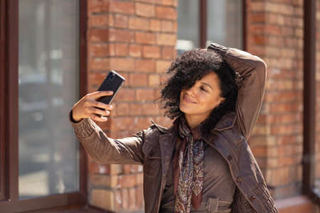 Portrait of stylish young African American woman making selfie on mobile phone. Brunette with curly hair in brown leather jacket posing on street against backdrop of blurred brick building. Close up.