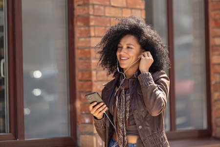 Portrait of young African American woman enjoying music with headphones using phone. Brunette with curly hair in leather jacket posing on street against backdrop of blurred brick building. Close up.