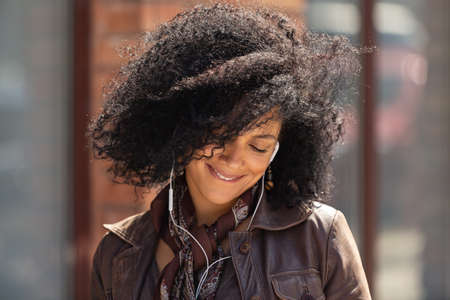 Portrait of young African American woman enjoying music with headphones. Brunette with curly hair in leather jacket posing on street against backdrop of blurred brick building. Close up.