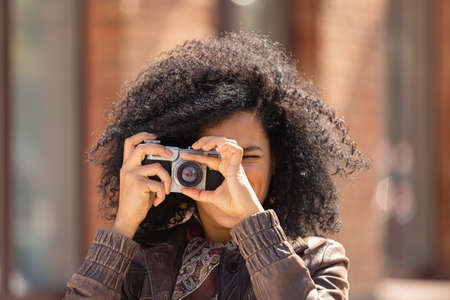 Stylish young African American woman taking pictures with a retro camera. Brunette with curly hair in brown leather jacket poses against background of blurred brick building. Close up.