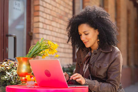 Portrait of stylish young African American woman typing on a laptop keyboard. Brunette in brown leather jacket sitting at a table in a cozy cafe on the street. Close up. 스톡 콘텐츠