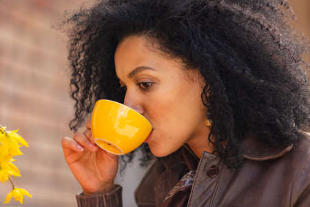 Portrait of stylish young African American woman enjoys aroma and taste of hot coffee in yellow cup. Brunette in brown leather jacket sitting at a table in a cozy cafe on the street. Close up.
