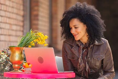Portrait of stylish young African American woman talking on video call using laptop. Brunette in brown leather jacket sitting at a table in a cozy cafe on the street. Close up. 스톡 콘텐츠