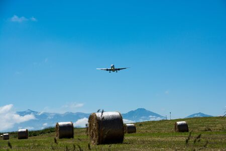 Hay bales and blue sky and jet airliner Banco de Imagens