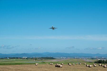 Mowed pasture field and a plane taking off