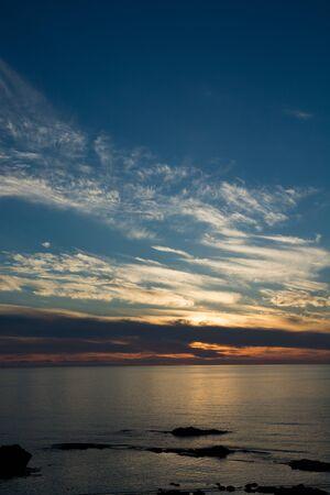 Beautiful calm sea dusk with sunset clouds